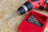 Electric Screwdriver With Drill Set, Red Electric Drill With Drill And Drill Set On Wooden Backgroun poster
