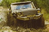 Mud And Water Splash In Off-road Racing. Offroad Vehicle Coming Out Of A Mud Hole Hazard. Drag Racin poster