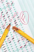 A graded test form with red scoring pencil marks indicates frustration and failure in the education