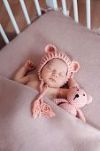 Beautiful Newborn Baby Girl Wearing Pink Hat And Peacefully Sleeping In Her Bed. poster