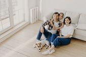Lovely European Family Of Father, Mother And Their Daughter Sit On Floor Near Sofa In Spacious White poster