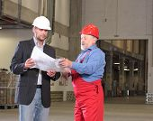 stock photo of construction industry  - two workers in warehouse businessmen and senior worker wearing hardhats looking at a set of blueprints and discussing a construction project - JPG