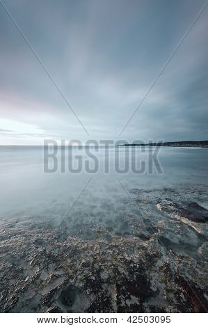 Submerged Rocks, Ocean And Cloudy Sky On Bay Beach