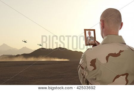 A soldier looks at the photo of the deceased friend