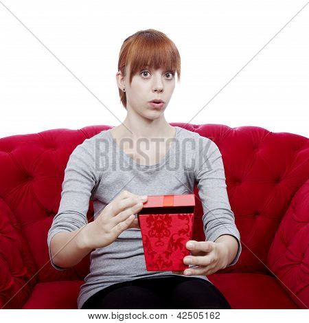 Young Beautiful Red Haired Girl Opens Gift Box For You On Red Sofa In Front Of White Background
