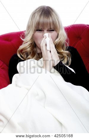 Young Beautiful Blond Haired Girl With Hanky And Illness On Red Sofa In Front Of White Background