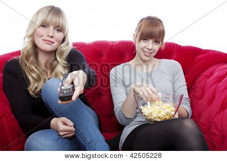 Young Beautiful Blond And Red Haired Girls On Red Sofa With Remote Control And Popcorn In Front Of W