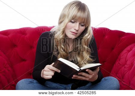Young Blond Haired Girl On Red Sofa Read A Book In Front Of White Background