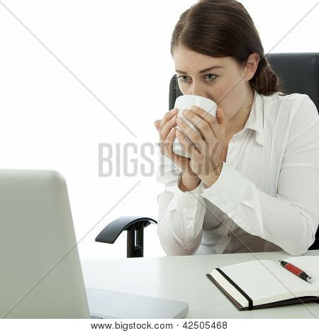 Young Brunette Business Woman Drinking Coffee In Front Of Computer