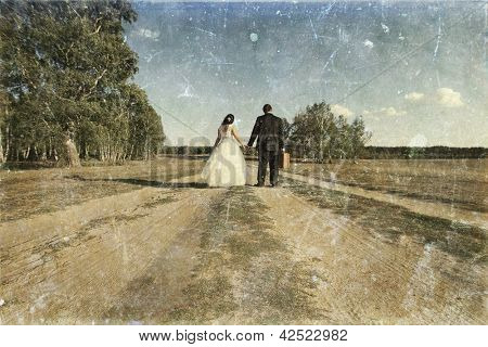 Vintage photo of newlywed couple walking away on dusty road