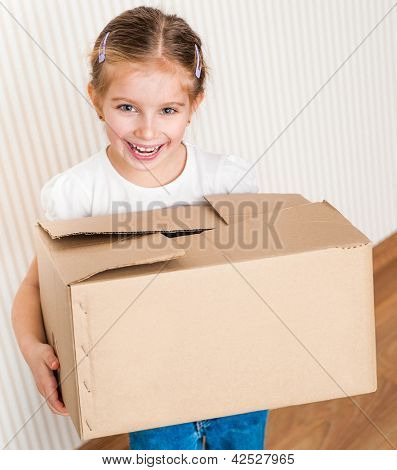 Little girl moving into new house, carrying cardboard box