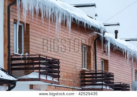 Overhanging Icicles On The House Roof Over Balconies