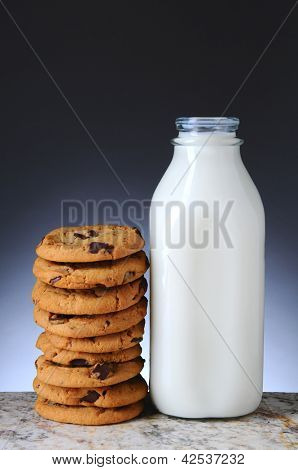 Closeup of an old fashioned glass milk bottle and a stack of chocolate chip cookies. Vertical format with a light to dark gray background.