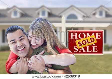 Happy Mixed Race Couple in Front of Sold Real Estate Sign and New House.
