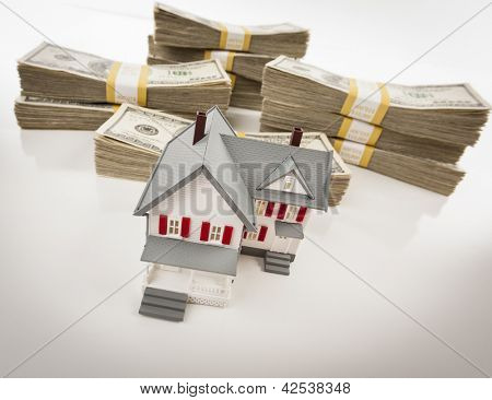 Stacks of One Hundred Dollar Bills with Small House.