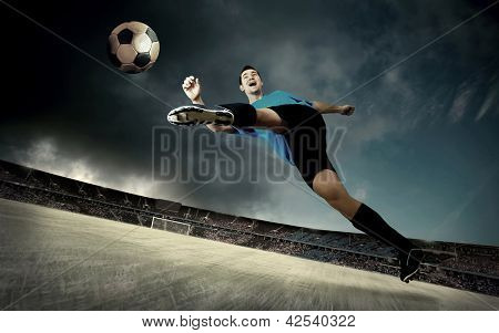 football player on soccer field of stadium with drammatic sky