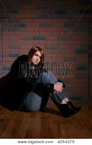 Bored Looking Teenage Girl Sitting Against Brick Background