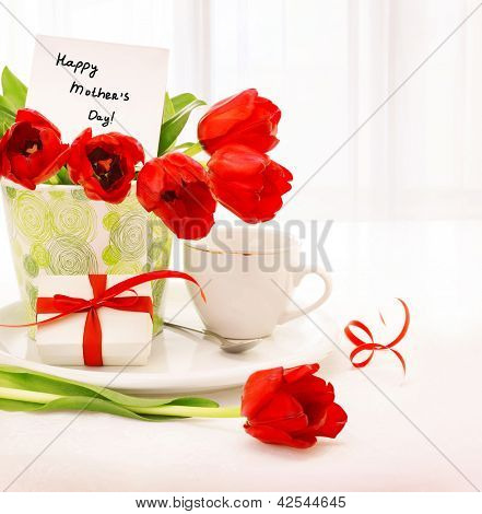Picture of beautiful tulips pot with gift box and cup of tea on the table at home, breakfast for mommy, happy mothers day, morning drink, romantic still life, indoor decorations, fresh red flowers
