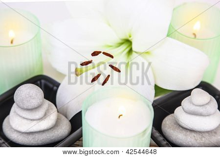 Photo of white lily flower, pebble stones, aromatic candles, closeup of spa still life, spa salon decorations, peace and meditation, herbal massage, zen balance, enjoying dayspa, beauty care