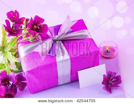 Image of pink giftbox with silk bow, fresh purple flowers, candle and blank postcard isolated on blur background, festive still life, happy mothers day, romantic holiday, love and romance concept