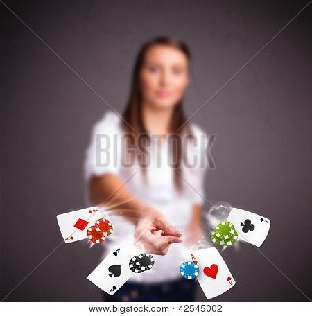 Pretty young woman playing with poker cards and chips
