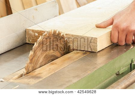 Carpenter working on woodworking machines in carpentry shop