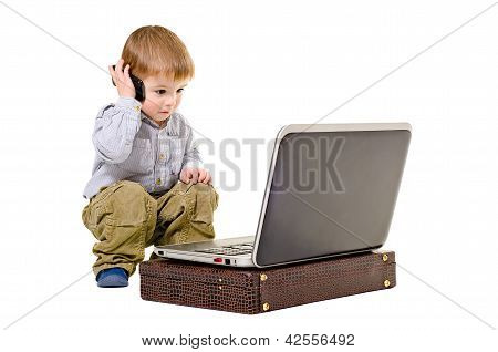 Cute little boy speaks on a mobile phone looking at laptop