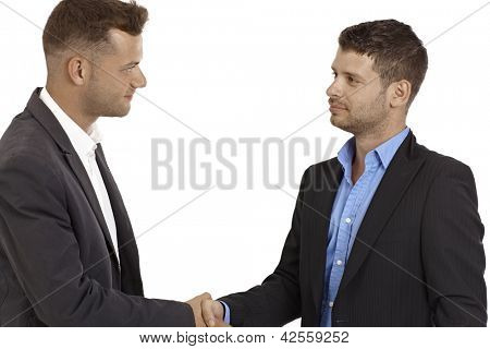 Young business partners shaking hands.