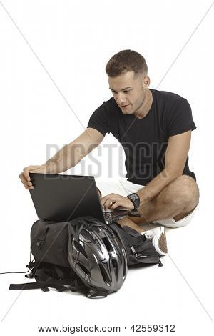Casual young man using laptop computer, having backpack and helmet, sitting in tailor seat.