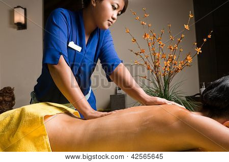 Young woman having Bali style massage at spa salon