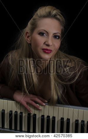 Sexy Lady In Bra And Leather Coat Posing With Synthesizer Over Black Background