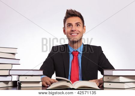 young business man sitting between books struck by an idea