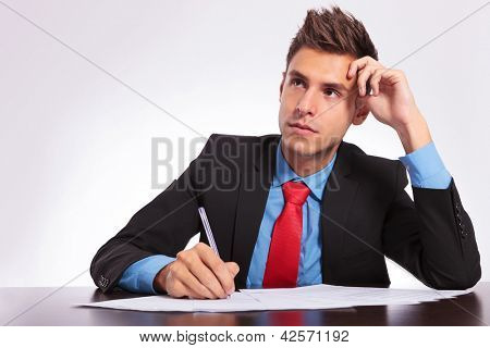 young business man sitting at the table thinking what to write