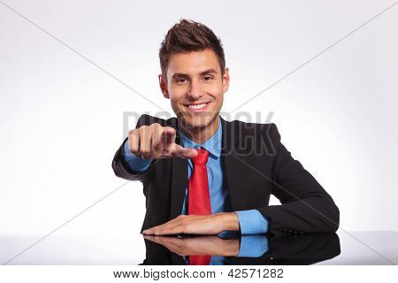 young business man is at the desk and is pointing and looking at the camera with a smile on his face