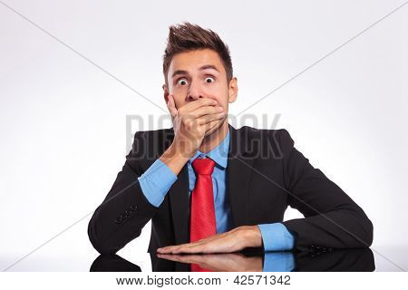 young business man sitting at the office and looking shocked at the camera covering his mouth with his hand