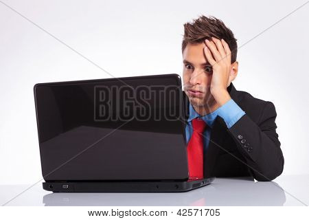 young business man sitting at desk is overwhelmed of too much work on his laptop