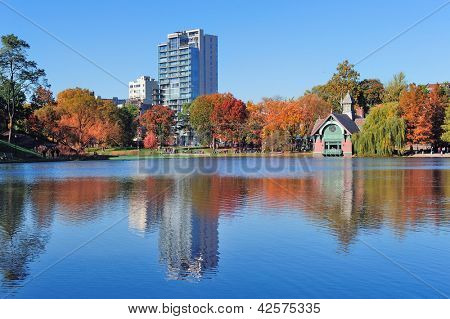 Autumn in Central Park north end in New York City Manhattan with buildings, lake and colorful foliage with clear blue sky.