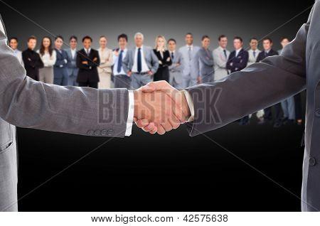 Geschäftsleute Händeschütteln mit Großunternehmen Team dahinter auf schwarzem Hintergrund