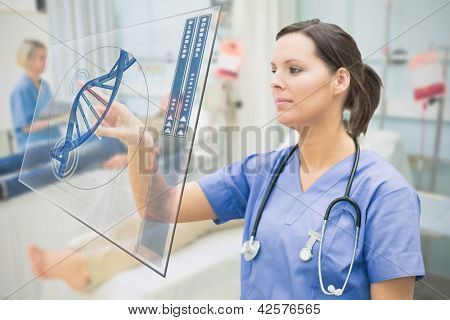 Nurse touching screen showing blue DNA helix data