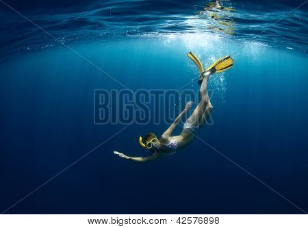 Underwater shoot of a young lady diving on a breath hold in a clear profound sea with sunbeams shining through the water