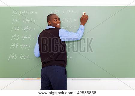 Profesor de la escuela de primaria hombre afroamericano borrar la pizarra