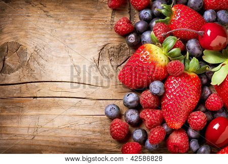 Berries on Wooden Background. Summer or Spring Organic Berry over Wood. Strawberries, Raspberries, Blueberry and Cherry. Agriculture, Gardening, Harvest Concept