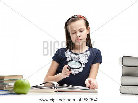 Little schoolgirl wonders about interesting material in the book, isolated, white background