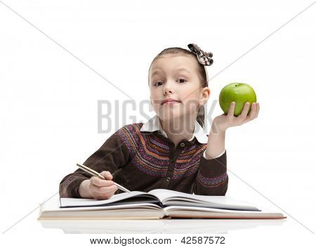 Schoolgirl with a green apple does her homework, isolated, white background