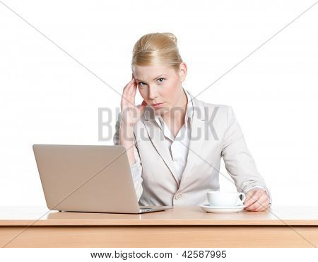 Young businesswoman sitting at a office table with laptop, isolated