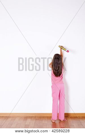 Little girl with a giant pencil writing on the wall