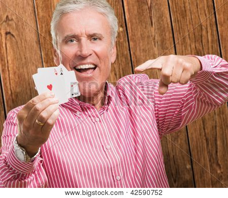 Mature Man Holding Playing Cards against a wooden background