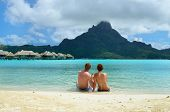 stock photo of pacific islands  - A honeymoon couple drinking a cocktail on the beach of a luxury vacation resort in the lagoon with a view on the tropical island of Bora Bora near Tahiti in French Polynesia - JPG