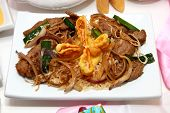 stock photo of mongolian  - Chinese crab rangoon and Mongolian beef on friend rice in kitchen or restaurant setting - JPG