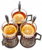 image of melchior  - top view of three vintage glasses in silver glass holders with black tea and lemon isolated on white background - JPG